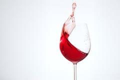 Läckert vin i ett exponeringsglas på en vit bakgrund Begreppet av Arkivfoton
