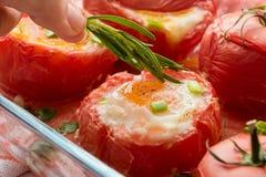 Läckra bakade välfyllda tomater med ägg och grönsaker arkivfoton