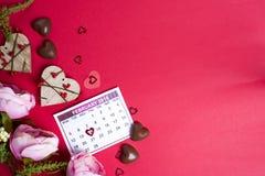 Läckra chokladgodisar och blommor på röd bakgrund Arkivfoto
