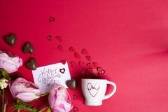 Läckra chokladgodisar och blommor på röd bakgrund Royaltyfri Bild