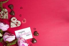 Läckra chokladgodisar och blommor på röd bakgrund Fotografering för Bildbyråer