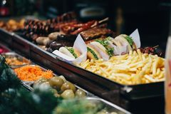 Läckra hamburgare, fransmansmåfiskar och korvar på feriegata M arkivfoto