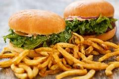 Läckra hamburgare på tabellen Royaltyfri Foto