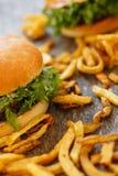 Läckra hamburgare på tabellen Arkivbild