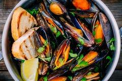 Läckra havs- musslor med med sås och persilja Citron och bagett Musslor i skalen arkivbilder
