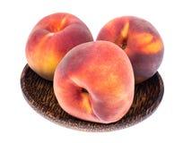 Läckra hela mogna persikor på träplattan Royaltyfria Foton