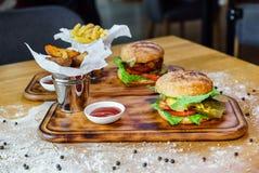 Läckra hemlagade hamburgare med en saftig kalvköttkotlett på en trätabell fotografering för bildbyråer