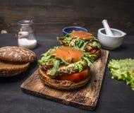 Läckra hemlagade hamburgare med höna i senapsgult sås med arugula och örter på en skärbrädagrönsallat och kryddor uppvaktar på Royaltyfri Fotografi