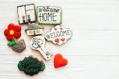 Läckra kakor för tangent, för hus, för växt, för fönster, för hjärta och för välkommet tecken på vitt trä, lägger framlänges med  royaltyfri foto