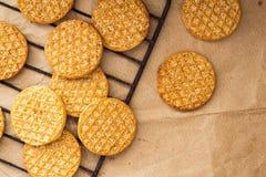 Läckra kakor och ett exponeringsglas av mjölkar på bakgrund för kraft papper arkivbilder
