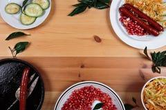 Läckra korvar med grönsaker på en träbakgrund Royaltyfri Foto
