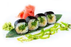 Läckra nya kortkort-rullar med alger av Chukka på en banan spricker ut Sushirullar på en vit bakgrund med ingefäran och wasabi Royaltyfria Foton