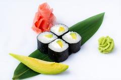 Läckra nya kortkort-rullar med avokadot och ost på en banan spricker ut Sushirullar på en vit bakgrund med ingefäran och wasabi Royaltyfri Fotografi