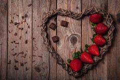 Läckra organiska jordgubbar med mörk choklad arkivbilder