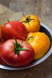 Läckra röda och gula tomater i en bunke Arkivfoton