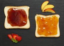Läckra rostade bröd med olika söta driftstopp på på kritiserar plattabakgrund royaltyfri fotografi