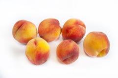 Läckra saftiga persikor på en vit bakgrund Arkivbild
