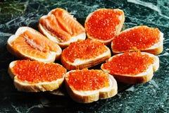 Läckra smörgåsar med den röda kaviaren på en platta Arkivbild