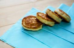 Läckra stekte pannkakor på en trätabell arkivfoton