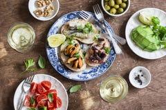 Läckra tapas - smörgåssardiner, musslor, bläckfisk, druva, oliv, tomat, avokado och vitt vin på trätabellen, bästa sikt royaltyfri fotografi