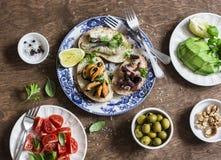 Läckra tapas - smörgåssardiner, musslor, bläckfisk, druva, oliv, tomat och avokado på trätabellen, bästa sikt fotografering för bildbyråer