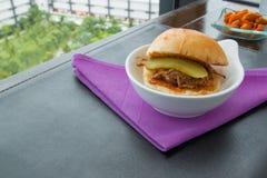Läckra tonfiskhamburgare på den violetta servetten, matbakgrunder Royaltyfri Bild