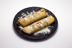 Läckra varma pannkakor på en svart platta som isoleras på en vit bakgrund Fotografering för Bildbyråer