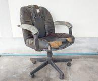 Läder för skada för svart kontorsstol smutsar ner gammalt och, tid att byta ut royaltyfri foto