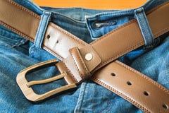 Läderbälte på jeansflåsanden Arkivbilder
