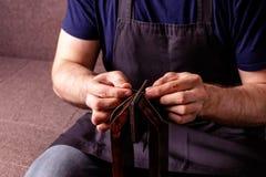 läderhantverk som anpassar processen - mäns händer som syr den bruna plånboken Fotografering för Bildbyråer