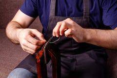 läderhantverk som anpassar processen - mäns händer som syr den bruna plånboken Royaltyfri Foto