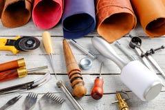 Läderhantverkhjälpmedel och redskap på träbakgrund Royaltyfri Foto