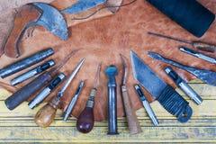 Läderhantverkhjälpmedel på en träbakgrund Skrivbord för lädercraftmansarbete Stycke av handgjorda hjälpmedel för skinn och för ar Royaltyfri Fotografi