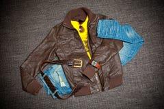 Läderomslag, jeans med ett bälte, skjorta, klockor och solglasögon Arkivbilder