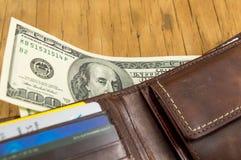 Läderplånbok- och dollarräkningar som ut faller Arkivbild