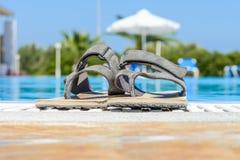 Lädersandaler är på kanten av simbassängen Royaltyfri Fotografi