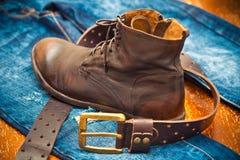 Läderskor, läderbälte med en guld- buckla, jeans Arkivbild