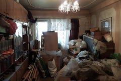 Lägenhet av en pensionär som skräpas ner med avfall och böcker Arkivfoto