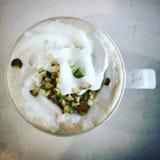 Lägenhet för bästa sikt som är lekmanna- av en varm cappuccino med muttrar och piskad kräm i en keramisk kopp Royaltyfri Bild