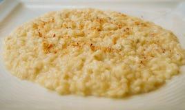 Lägenhet-lekmanna- av den läckra krämiga risottobunken med parmesanost på den vita plattan Royaltyfri Bild