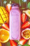 Lägenhet-lekmanna- av färgrika smoothies i flaskor med tropisk frukt och superfoods royaltyfri foto