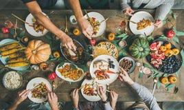 Lägenhet-lekmanna- av vänner som festar på tacksägelsedagtabellen med kalkon royaltyfria foton