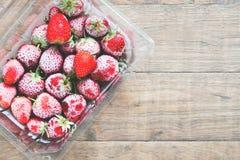 Lägenhet som är lekmanna- av djupfrysta jordgubbar i ask på träbakgrund Royaltyfri Bild