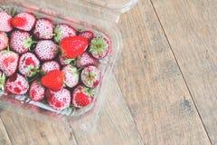 Lägenhet som är lekmanna- av djupfrysta jordgubbar i ask på träbakgrund Fotografering för Bildbyråer