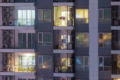 Lägenhetavskildhetsbegreppet på natten med belysning och elektricitet använder årlig stigning Lägenhetfönster på natten royaltyfri fotografi