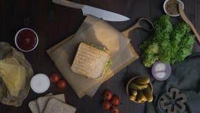 Lägenheten lägger av smörgåsen med skinka, och sallad på träbrädet i strålen av ljus, kockens hand slutför smörgåsen stock video