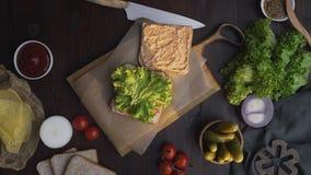 Lägenheten lägger av smörgåsen med skinka, och sallad på träbrädet i strålen av ljus, kockens hand slutför smörgåsen lager videofilmer