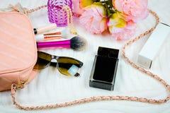 Lägenheten lägger med kvinnligt påse-, skönhetsmedel-, solglasögon-, parfume- och framsidapulver Modebegrepp på vit bakgrund royaltyfri bild