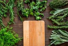 Lägenheten lägger med ny örter och grönska för att torka och framställning av kryddauppsättningen på träkökbakgrundsmodell royaltyfria foton