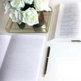 Lägenheten lägger med olik tillbehör; blommabukett, vita rosor, öppen bok, bibel arkivbild
